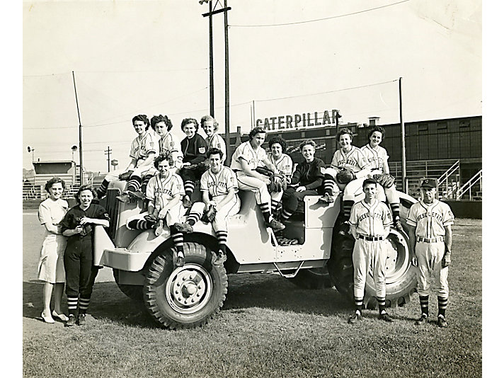 1945 Team sits on a wheeled tractor with Building HH in the background in East Peoria, Illinois.