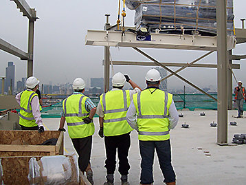 Men on building site providing project management expertise whilst watching a generator set being lifted by crane