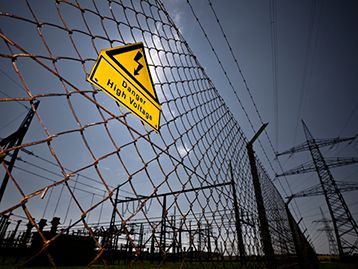 High voltage electric fence with warning sign