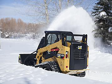 Caterpillar machine plowing snow