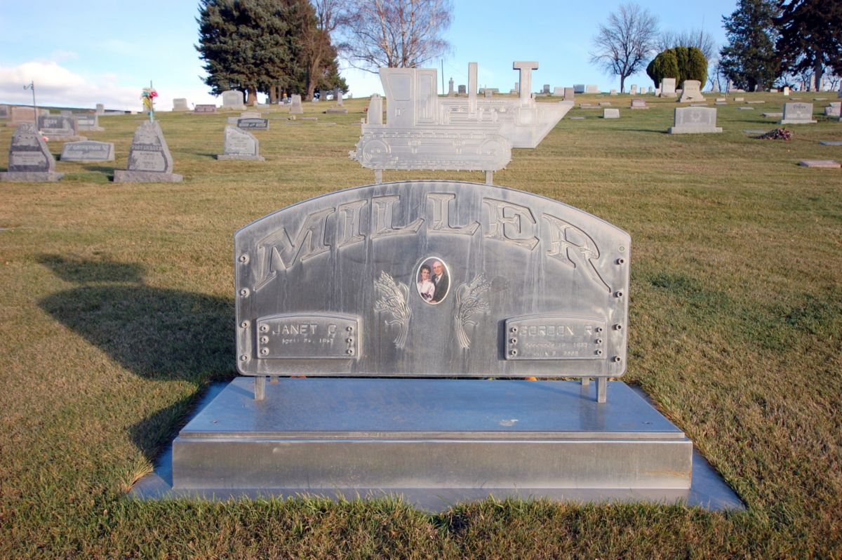 Gordon Miller's stainless steel headstone in the St. John Cemetery, featuring a D7 with distinctive Whitman County nose scoop. The piece was fabricated in the family's machine shop.