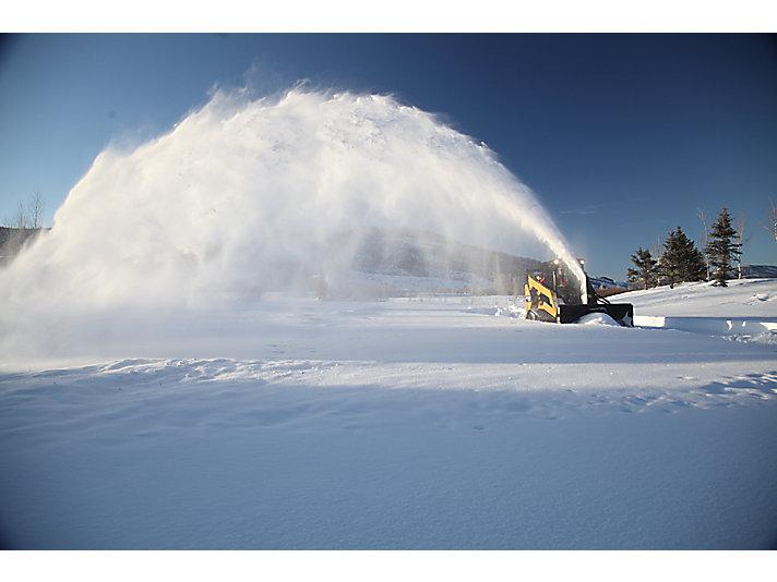 Quitanieves SR118 Cat® expulsando nieve a la distancia máxima