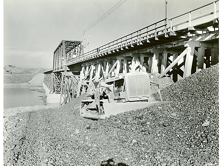 Caterpillar Diesel Seventy-Five track-type tractor equipped with a dozer leveling gravel at the Fort Peck Dam project in 1935.