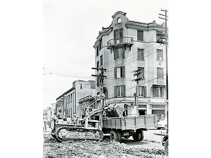 Diesel D4 track-type tractor with Trackson IT4 Traxcavator loading trucks in street widening project in heart of Sao Paulo, Brazil, 1949