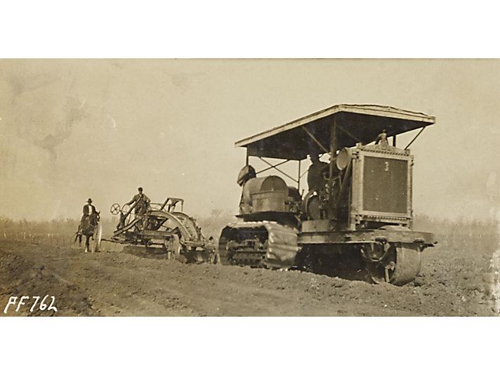 Holt Caterpillar Peoria model tractor pulling a grader, ca. 1914