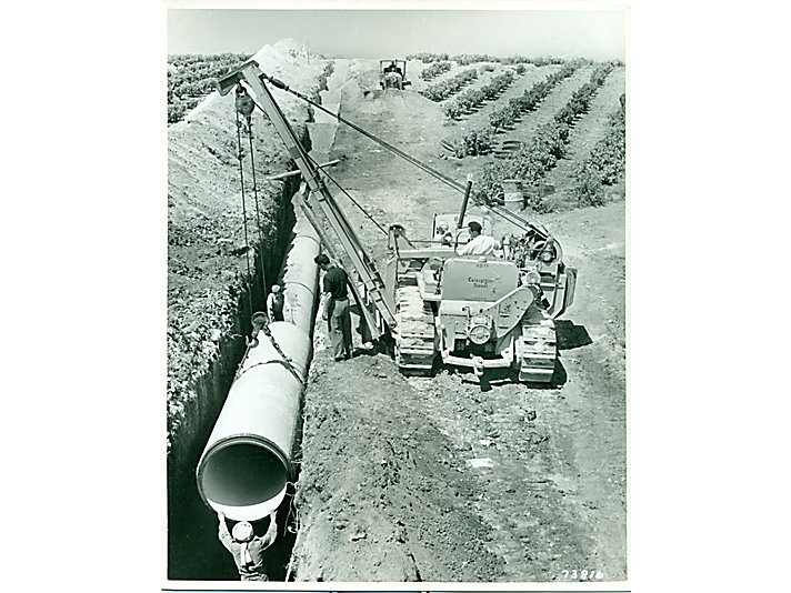 A Caterpillar D7 tractor with a pipelayer attachment in North Africa.