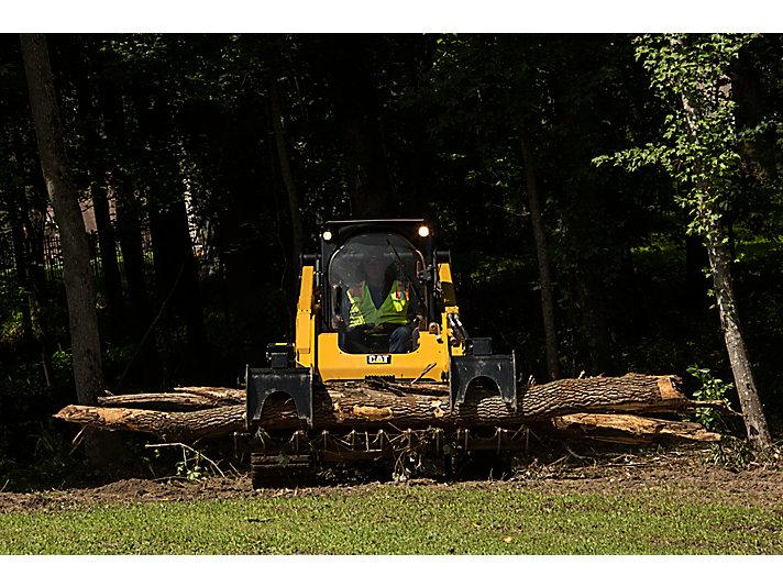 Rastrillo de garfio Cat® quitando troncos caídos