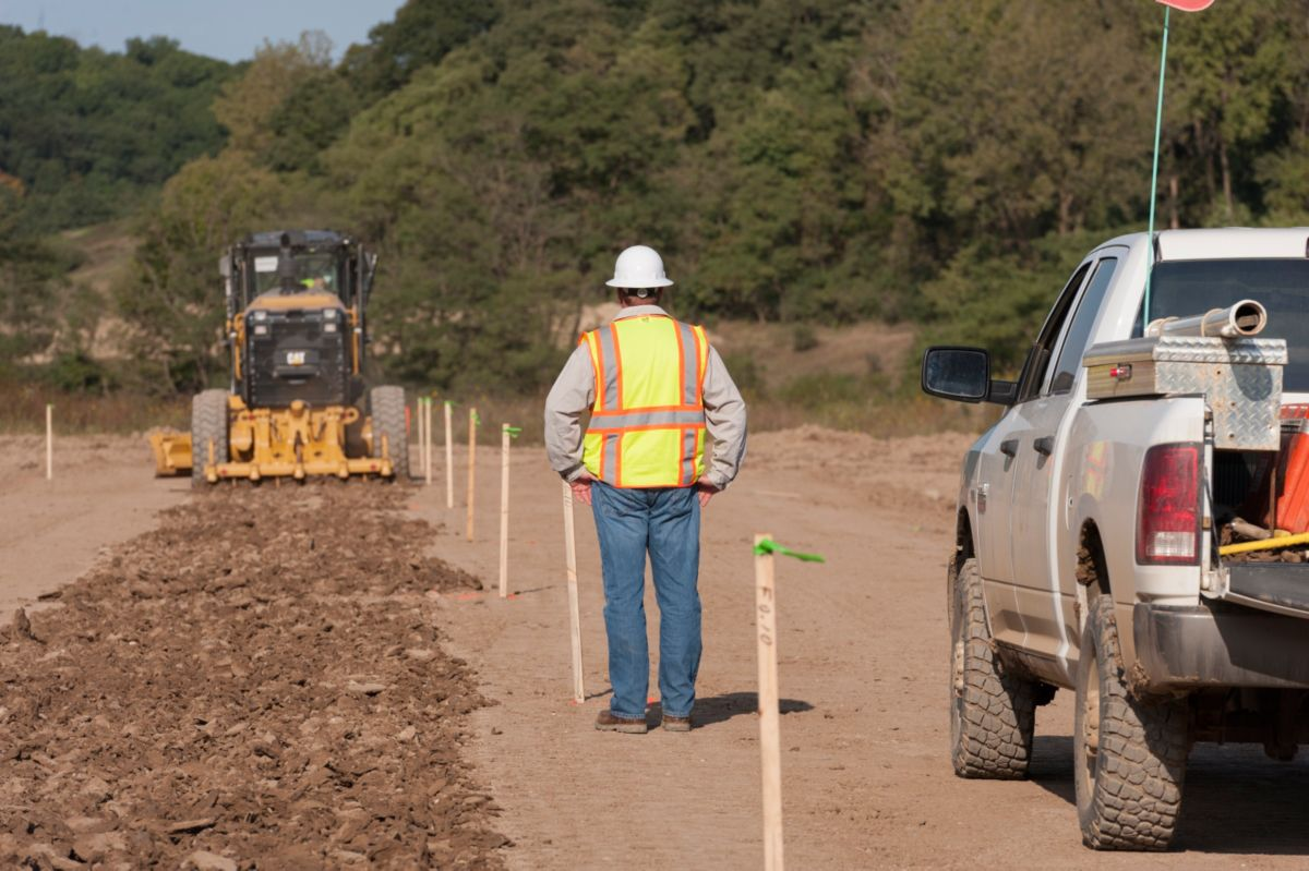 A motor grader scarifies the existing ground to prepare for compaction and fill. Without AccuGrade™ technology, between 250-300 stakes have to be set per mile for a typical four-lane highway.