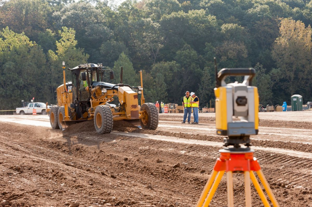 A motor grader uses Universal Total Station (UTS) to finish grade dirt subgrade in preparation for aggregate base course.