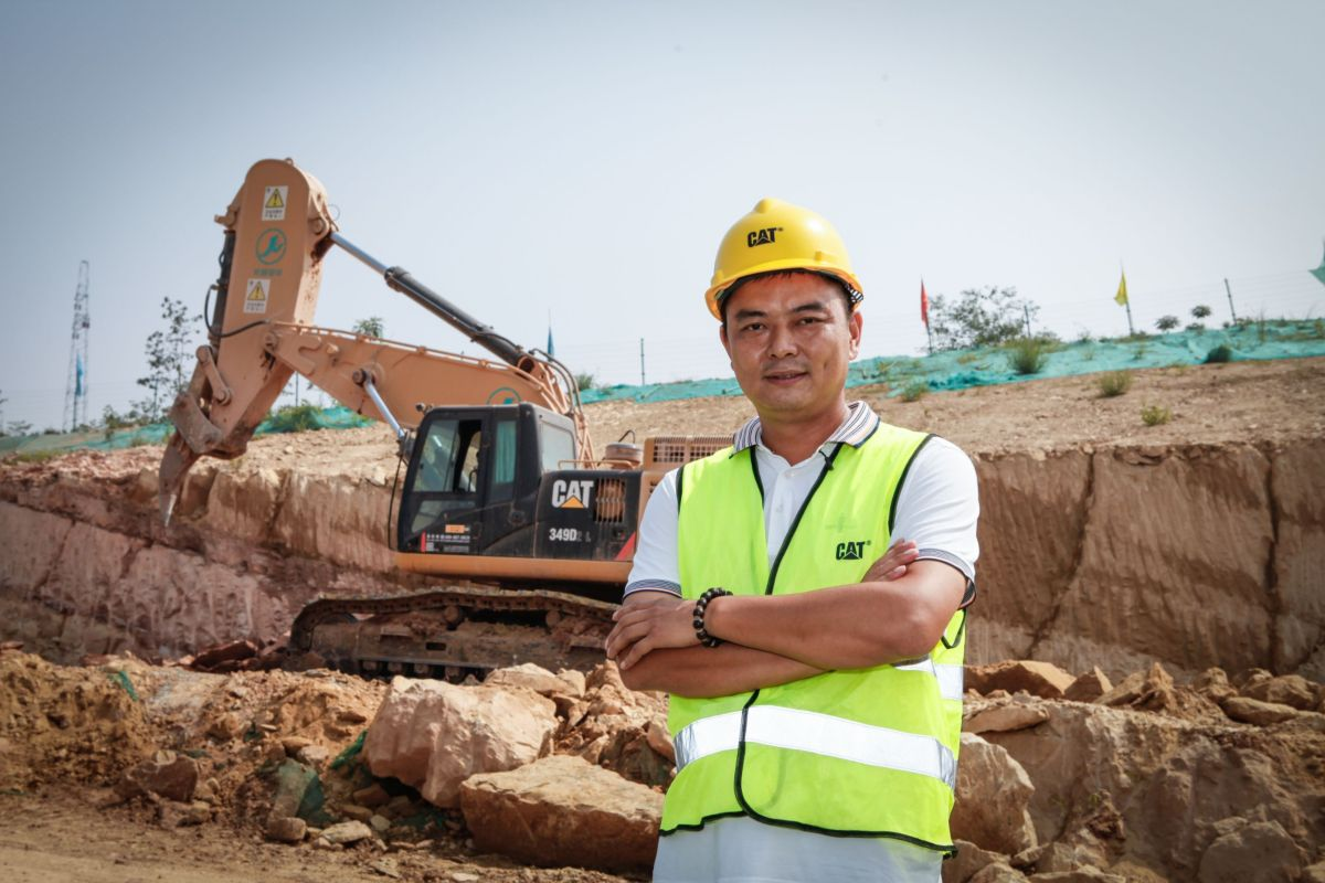 Chen Hu, owner of Sanhe Rental, stands in front of one of his frontless hydraulic excavators purchased through Caterpillar OEM Solutions, fitted with a rock arm and ripper for a special application.