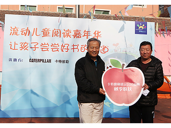 卡特彼勒全球副总裁、卡特彼勒(中国)投资有限公司董事长陈其华先生向新龙学校校长赠送卡特彼勒公益林收获苹果