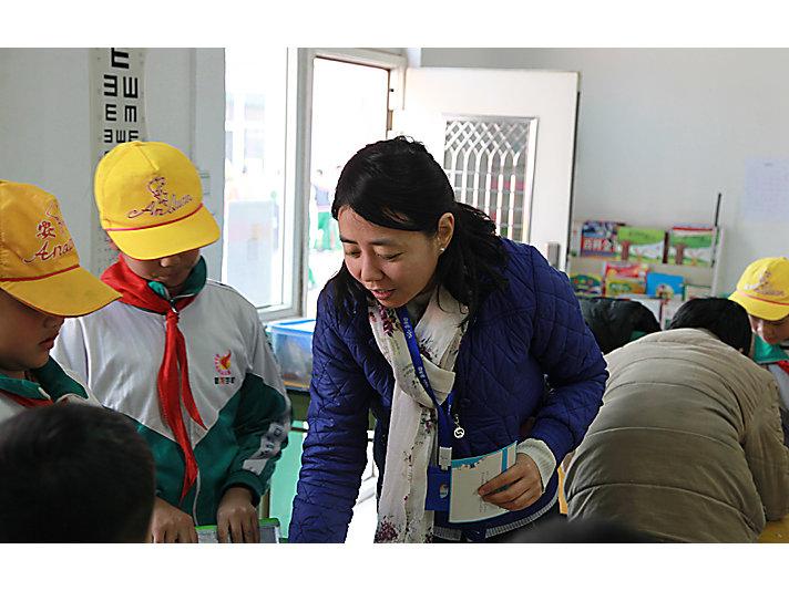 卡特彼勒志愿者和新龙学校学生一起读书做游戏