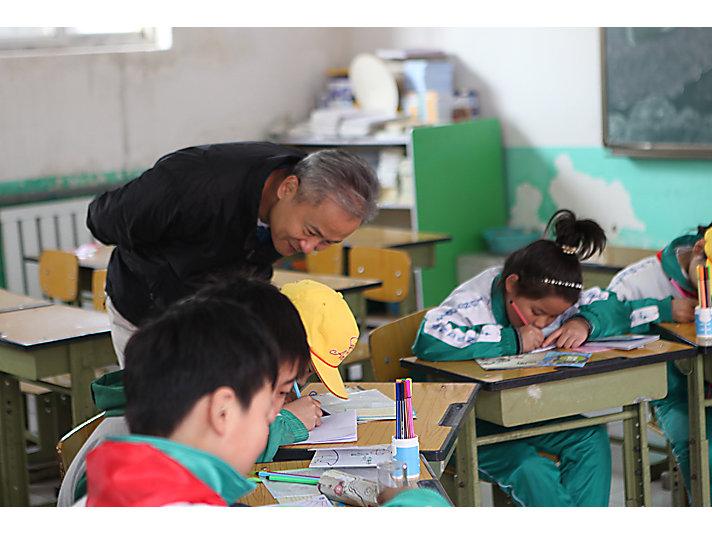 卡特彼勒志愿者和新龙学校学生一同读书