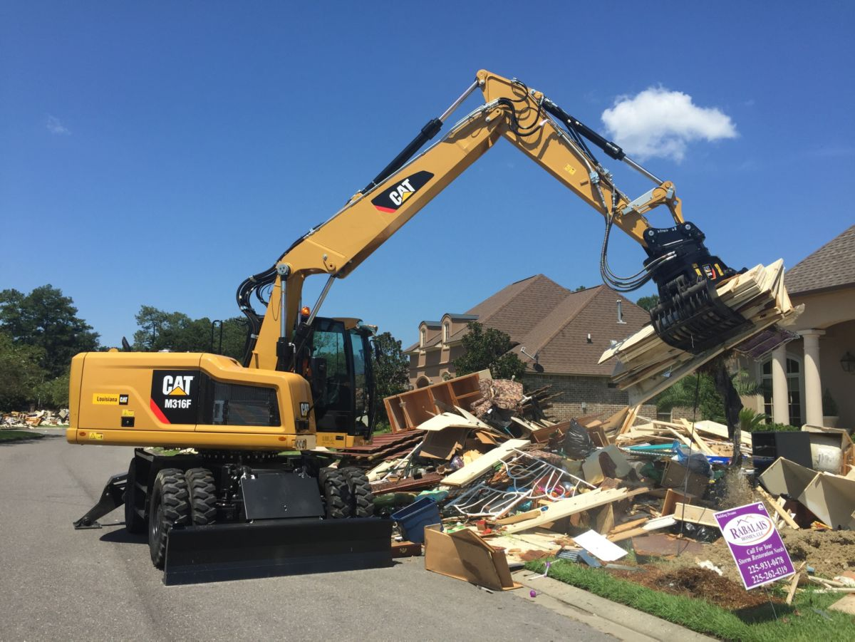 A Cat® M316F Wheeled Excavator picks up debris in a residential neighborhood affected by the historic floods in southern Louisiana.