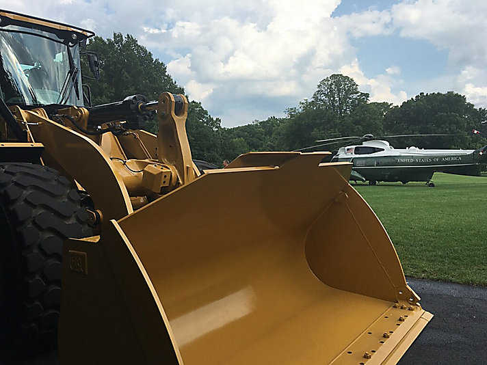 A Cat® 966M wheel loader on the South Lawn of the White House, with Marine One in the background.
