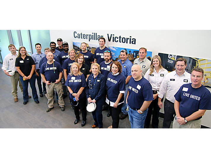 Employees from San Antonio, Schertz and Seguin pose with colleagues from Victoria after serving lunch to returning Caterpillar Victoria employees.