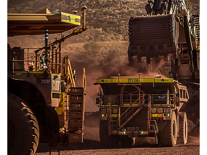 Two Cat 793F CMD autonomous trucks operating at Fortescue iron ore mine.