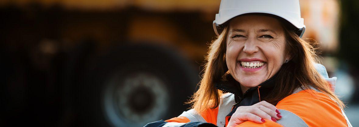 Un operaio solitario sorride alla telecamera indossando un casco e un giubbotto catarifrangente