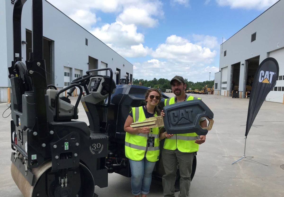 "Jaimee and Andrew Mallett holding the ""key"" to their new Cat CB24B small tandem vibratory roller."