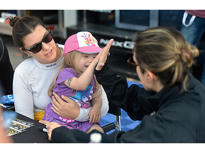 High fives all around for an IMSA fan with No. 57 drivers Ana Beatriz and Katherine Legge.