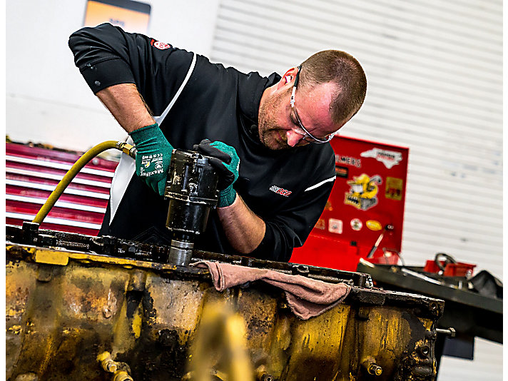 RCR technician Blake Zobrist helps remove a crankshaft from a C18 engine.