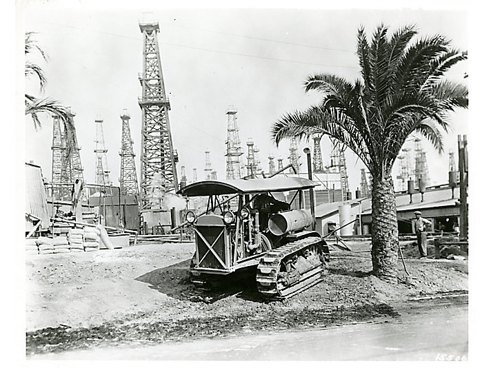 Caterpillar Sixty tractor packing down loose dirt by using its tread in a California oilfield in 1929.