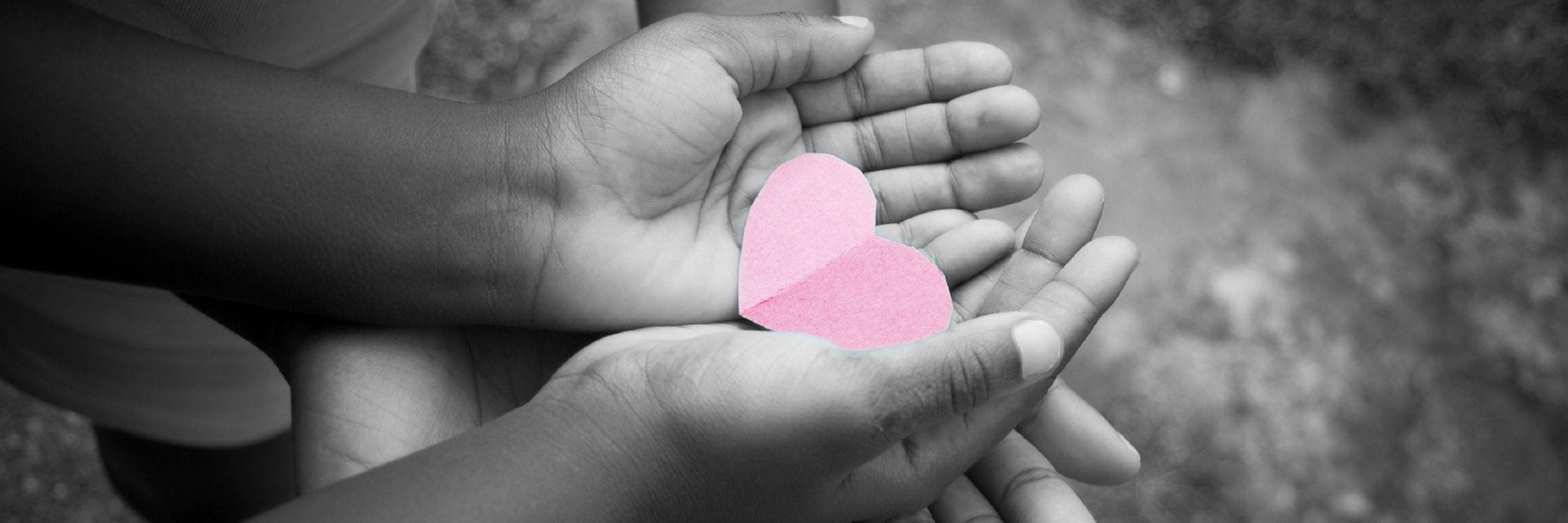 des mains tenant le cœur en papier