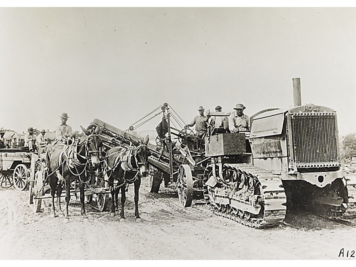 Holt Ten Ton track-type tractor working with horses while grading a road in California, circa 1920.