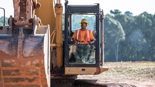 Man in sunglasses and hardhat operating construction equipment