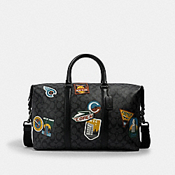 TREKKER BAG IN SIGNATURE CANVAS WITH TRAVEL PATCHES - QB/CHARCOAL BLACK - COACH 2329