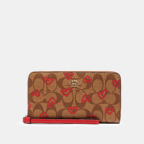 COACH LARGE PHONE WALLET IN SIGNATURE CANVAS WITH CRAYON HEARTS PRINT - IM/KHAKI RED MULTI - 91578