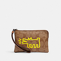 KEITH HARING CORNER ZIP WRISTLET IN SIGNATURE CANVAS - QB/KHAKI SADDLE - COACH F12998