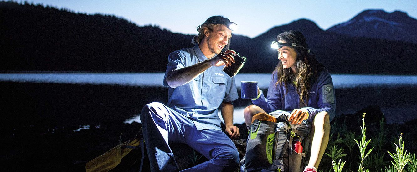 A young man and woman wearing stream lights on their heads share a beverage while camping at night