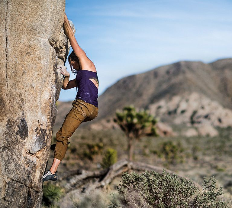 Woman climbing side of rock wall