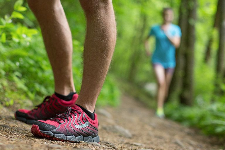 Two runners on a hot, summer trail wearing Montrail running shoes with mesh uppers.