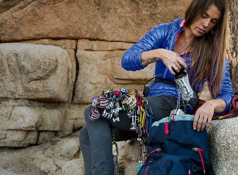 A climber wearing a super-light Ghost Whisperer down jacket is preparing her gear.