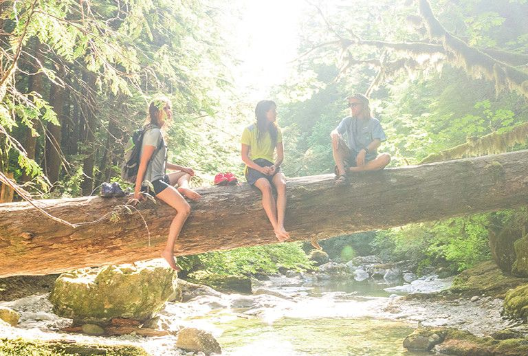 Three hikers take a break on a log that is over a creek