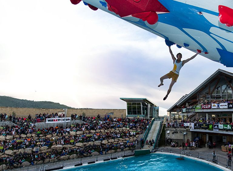 Man hangs from rock climbing wall situated over an Olympic sized swimming pool.