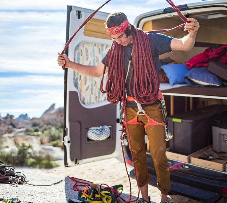 Man standing outside a van getting ready to rock climb.
