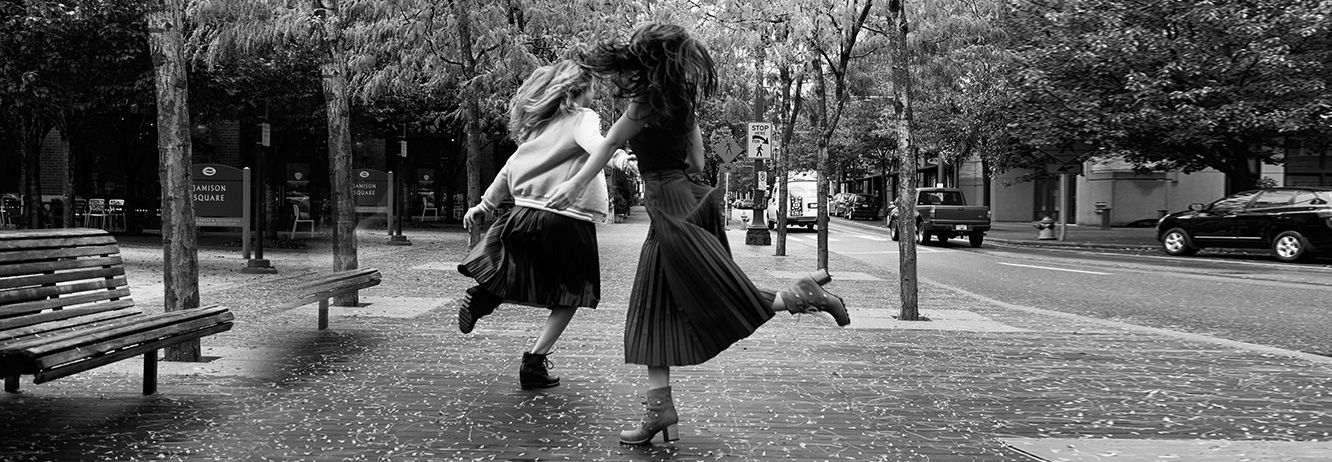 Two girls dancing in the street.