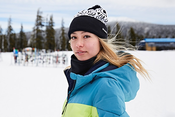 Woman at a ski resort in a Columbia beanie and gaiter.