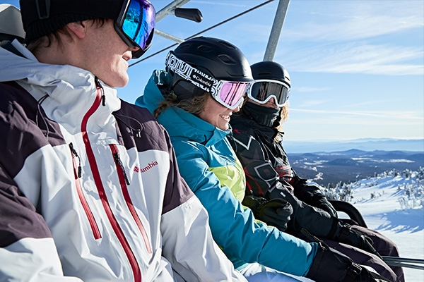 Three friends on the chairlift on a sunny day.