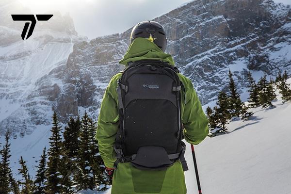 Skier in Titanium gear overlooking backcountry. Titanium logo.