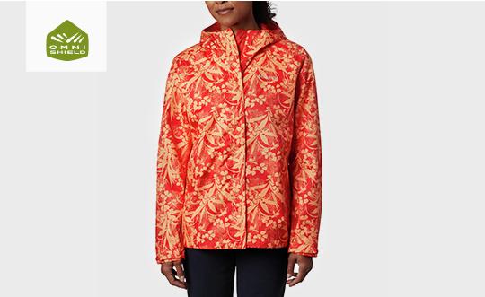 A woman in an orange patterned Ridge Gates jacket. Omni-Shield logo.