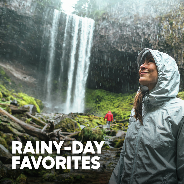 A man and woman in rain jackets exploring mossy boulders at the bottom of a waterfall in the rain. Rainy-Day Favorites.