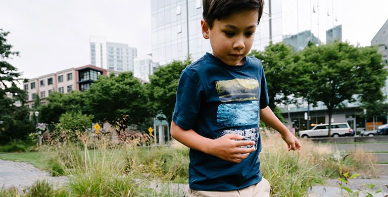 A boy in a tee in a city park.