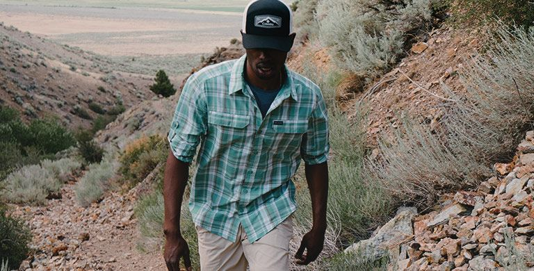 A man hiking in a short sleeve shirt.