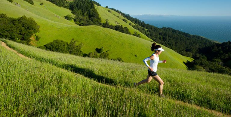 Woman running on a trail through a field