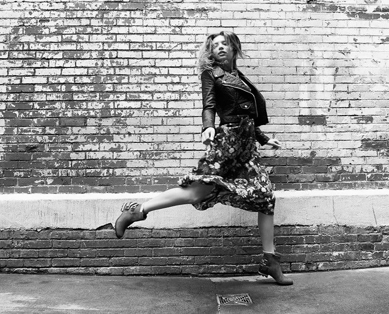 A young woman in boots running on a sidewalk against a brick wall.