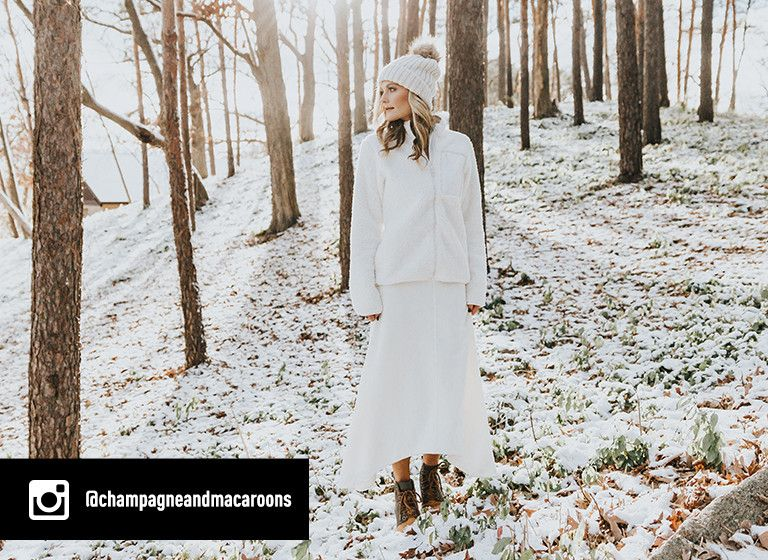 Instagram image of @champagneandmacaroons dressed in all white walking though a snowy forest in the 1964 Premium Wedge